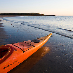 A kayak on the beach at dawn at the Shifting Lots Preserve in Plymouth, Massachusetts.  Owned by the Wildlands Trust.  Cape Cod Bay.  Near Ellisville Harbor State Park.