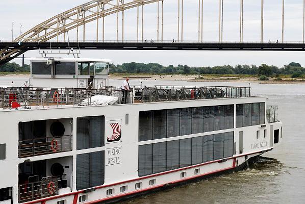 Nederland, Nijmegen, 29-7-2018 Passagiersboot van een rijncruise vaart op de Waal, Rijn. De stuurman vaart het schip weg van de kade via een bedieningspaneel dat aan de stuurboordzijde van het schip ingebouwd zit. Zo kan hij goed zien hoe de boot loskomt van de wal . De man is van Homngarije, een hongaarse stuurman, hongaars bemanningslid.Foto: Flip Franssen