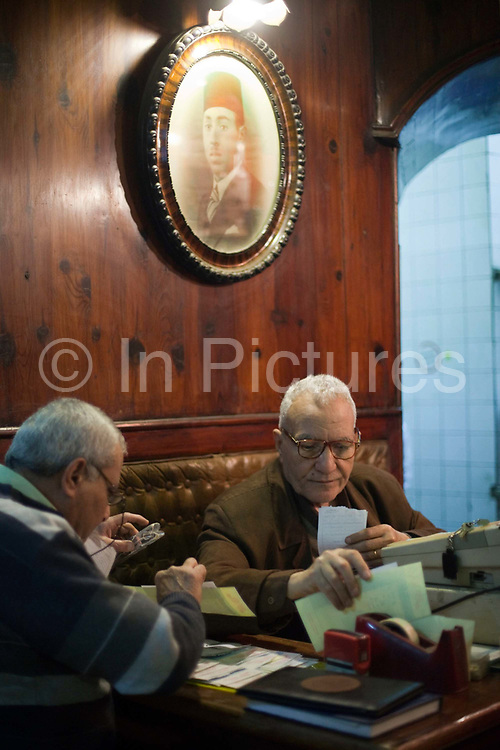 Cashiers at the Cafe Riche tally their bills after a rally in Tahrir Square, Cairo, Egypt