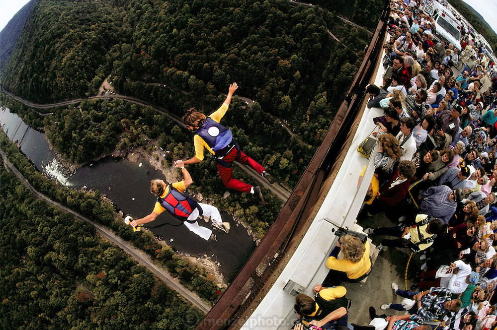"BASE jumping from New River Gorge bridge, Bridge Day, West Virginia, USA. BASE jumping is the sport of using a parachute to jump from fixed objects. ""BASE"" is an acronym that stands for the four categories of objects from which one can jump; (B)uilding, (A)ntenna (an uninhabited tower such as an aerial mast), (S)pan (a bridge, arch or dome), and (E)arth (a cliff or other natural formation). BASE jumping is much more dangerous than skydiving from aircraft and is currently regarded as a fringe extreme sport. -from Wikipedia."
