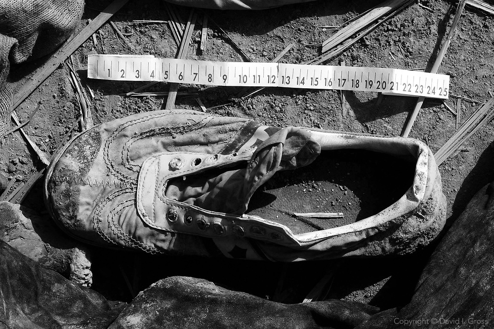 A child's shoe lies among the remains of hundreds of people found in a swampy area near Hillah, Iraq. The people were killed by the regime of Saddam Hussein. The measuring tape was put down by the photographer, for scale.