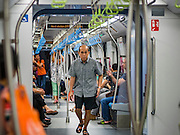 "27 DECEMBER 2015 - SINGAPORE, SINGAPORE:  A man walks through the train on the expanded Downtown Line on the first day of service on the new line. Singapore opened the extension of the Downtown Line on its subway system Sunday. The extension is a part of Singapore's plans to make the city-state a ""car lite"" metropolis with plans to double the current subway to more than 360 kilometers of track by 2030. The government plans to have 80% of homes within a 10 minute walk of a subway station.   PHOTO BY JACK KURTZ"
