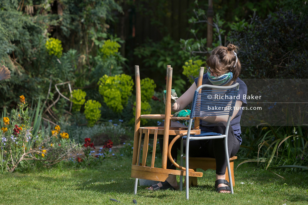 On the second day of the Easter Bank Holiday during the  lockdown, a restriction imposed by the UK government during the Coronavirus pandemic, a young woman wearing a scarf around her mouth against fine dust, rather than viral droplets, rubs down an old chair with sandpaper in the garden of a suburban home in south London, on 11th April 2020, in London, England.