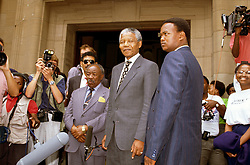 NELSON ROLIHLAHLA MANDELA (July 18, 1918 - December 5, 2013), 95, world renown civil rights activist and world leader. Mandela emerged from prison to become the first black President of South Africa in 1994. As a symbol of peacemaking, he won the 1993 Nobel Peace Prize. Joined his countries anti-apartheid movement in his 20s and then the ANC (African National Congress) in 1942. For next 20 years, he directed a campaign of peaceful, non-violent defiance against the South African government and its racist policies and for his efforts was incarcerated for 27 years. Remained strong and faithful to his cause, thru out his life, of a world of peace. Transforming the world, to make it a better place. PICTURED: NELSON MANDELA, ANC leader with ALFRED NZO and bodyguards outside the Johannesburg High Court. South Africa. 1991-1993. (Credit Image: © Greg Marinovich/ZUMA Wire/ZUMAPRESS.com)