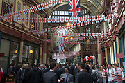 Drinkers gather in Leadenhall Market on St George's Day (April 23rd), when 'Englishmen' celebrate their patron saint. Flags and bunting hangs above their heads as pints of beer are consumed this lunchtime. Leadenhall Market is a covered market in London, located on Gracechurch Street with additional pedestrian access via a number of narrow passageways. It is one of the oldest markets in London, dating back to the 14th century and formed part of the marathon course of the 2012 Olympic Games plus the location for Diagon Alley in Harry Potter and the Philosopher's Stone. The ornate roof structure, painted green, maroon and cream, and cobbled floors of the current structure, designed in 1881 by Sir Horace Jones