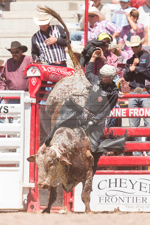 Bull rider Jeff Bertus hangs on during the Bull Riding finals at the Cheyenne Frontier Days rodeo in Frontier Park Arena July 26, 2015 in Cheyenne, Wyoming. Frontier Days celebrates the cowboy traditions of the west with a rodeo, parade and fair.