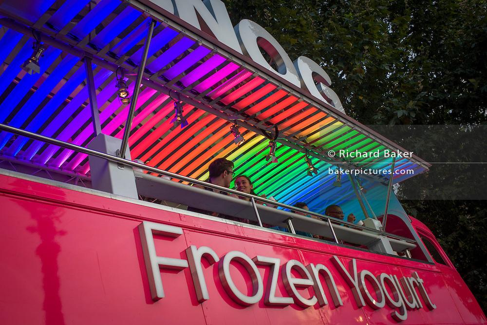 Young couple enjoy frozen yoghurt at a mobile kiosk on London's Southbank.