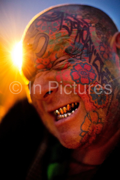"""Mad Alan, """"explorer"""", with his tatooed face & titanium teeth.<br /> Shangri-La is the after-hours epicentre of the Glastonbury Festival 2013. The theme for 2013 is Afterlife with the visiters choice between heavan and hell. Glastonbury is the world's biggest greenfield festival with nearly 200,000  visiters camping in the dairy farm of Michael Evis in Somerset, UK.<br /> The first festival was in 1970 and was influenced by hippie ethics and the free festival movement. The festival retains vestiges of this tradition such as the Green Fields area which includes the Green Futures and Healing Field."""