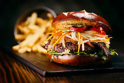 """SHOT 6/11/15 3:19:14 PM - Ophelia's Electric Soapbox Brothel Burger with Yak, Korean BBQ sauce, Miso Candied Bacon, Ponzu Onions, Pickled Vegetables on a Pretzel Bun $15. Ophelia's is a multilevel """"gastro-brothel"""", bar and music venue offering eclectic American food. (Photo by Marc Piscotty / © 2015)"""