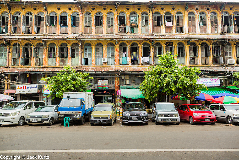 08 JUNE 2014 - YANGON, MYANMAR: A colonial building on Lanmadaw Road in Yangon has restaurants on the ground floor and tenement apartments on the upper floor. Yangon has the highest concentration of colonial style buildings still standing in Asia. Efforts are being made to preserve the buildings but many are in poor condition and not salvageable.   PHOTO BY JACK KURTZ