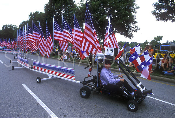 Stock photo of a tiny car pulling a long line of American and Texas flags