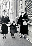 two adult woman with a little child standing outside France 1962