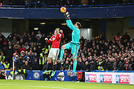 Wayne Rooney of Manchester United jumps with Chelsea's Goalkeeper Thibaut Courtois during the Barclays Premier League match between Chelsea and Manchester United at Stamford Bridge, London, England on 7 February 2016. Photo by Phil Duncan.