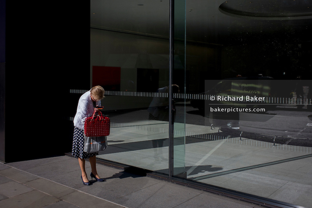 A woman searches at the bottom of her bag in front of an office foyer window in the City of London, the capital's financial district and oldest quarter.