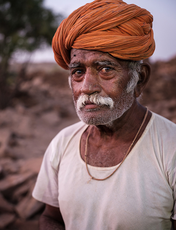 """JAISALMER, INDIA - CIRCA NOVEMBER 2018: Portrait of shepherd outside the ruins of Khabha Fort in Jaisalmer. Jaisalmer is also called """"The Golden City, and it is located in Rajasthan.  The town stands on a ridge of yellowish sandstone, and is crowned by the ancient Jaisalmer Fort."""