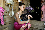 A young Laoseng ethnic minority woman with her baby outside her home in Ban Sopkang, Phongsaly province, Lao PDR. The remote and roadless village of Ban Sopkang is situated along the Nam Ou river and will be relocated due to the construction of the Nam Ou Cascade Hydropower Project Dam 7.