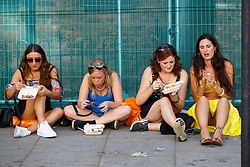 © Licensed to London News Pictures. 29/08/2016. London, UK. Revellers eat in public on the second day of Notting Hill Carnival in west London, Monday 29 August 2016. Photo credit: Tolga Akmen/LNP