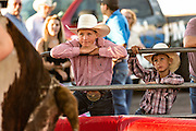 Young cowboys watch a rider on a mechanical bull at Cheyenne Frontier Days July 25, 2015 in Cheyenne, Wyoming. Frontier Days celebrates the cowboy traditions of the west with a rodeo, parade and fair.