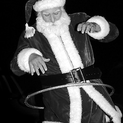 Russell Bissonnette entertains children with a hula hoop outside his Half Moon Bay apartment before his appearance as Santa Claus at the Miramar Beach Restaruant Christmas Party in Half Moon Bay on Monday night, Dec. 20, 2004.                               ..Photo by David Calvert<br />