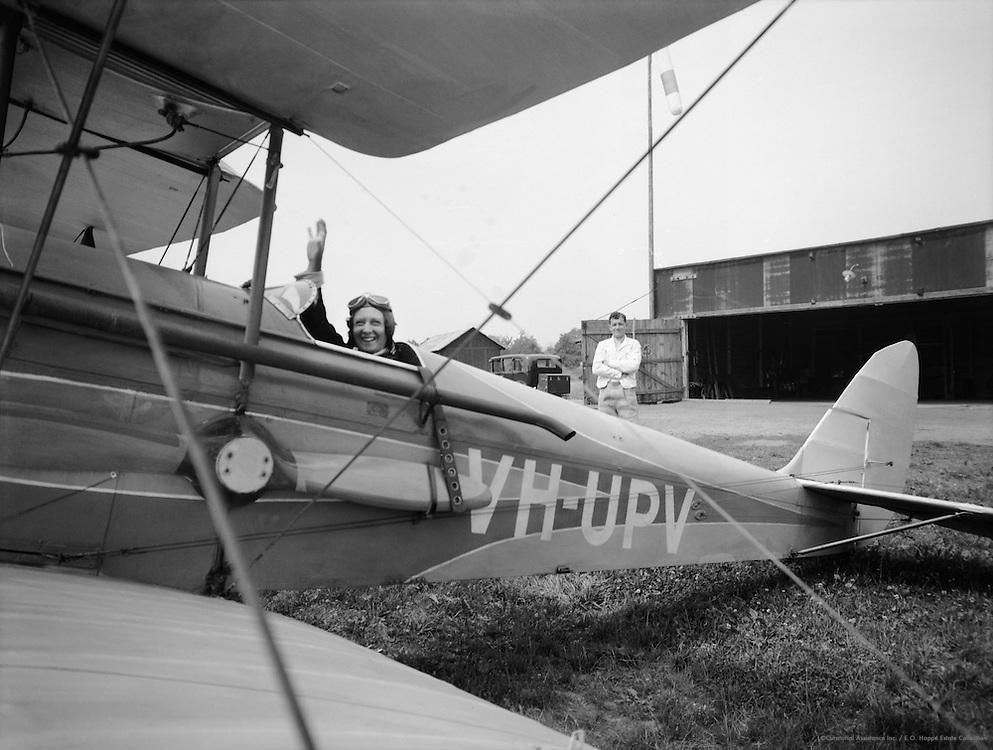 Lores Bonney, Australian pioneering aviatrix waving from her plane, a De Havilland Gypsy Moth, 1933