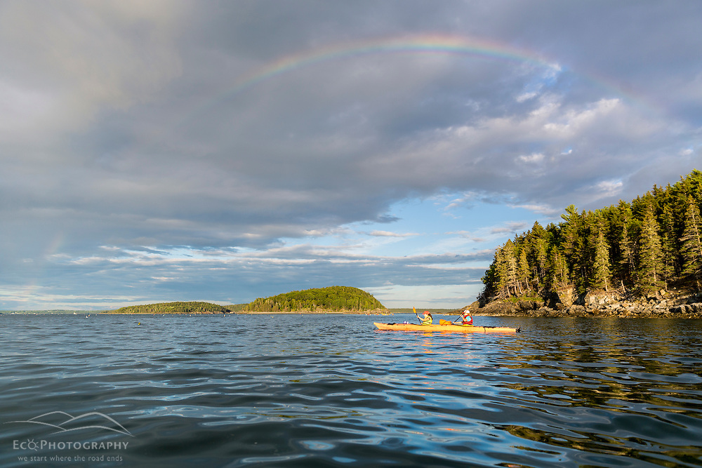A woman and her daughter sea kayaking under a rainbow in Frenchman Bay, Acadia National Park, Maine. Porcupine Islands.