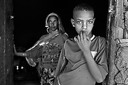 A boy and his Grandmother photographed at their home, near Harare, Ethiopia. There were an estimated 539,000 AIDS orphans (children having lost one or both parents) in Ethiopia in 2003; a cumulative total of 90,000 adults and 25,000 children had died of AIDS by end of 2003