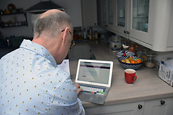 Man doing the 2021 England & Wales Census online - this takes place every 10 years. Scotland have postponed their census to 2022 due to Covid. March 2021. Posed by model