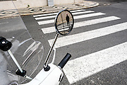 A man seen in a scooter rearviewmirror in a street in Lisbon.