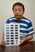 Hisao Manabe, CEO of Momotaro Jeans, holding a chart showing traditional Japanese indigo-dyeing shades, Kojima, Kurashiki City, Okayama Prefecture, Japan, July 11, 2013. Kojima is the birthplace of Japanese denim and famous for artisan jeans. The area's textile industry is based on advanced dyeing and weaving technology that has it's roots in pre-industrial indigo dyeing.