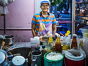17 JANUARY 2016 - BANGKOK, THAILAND: A woman in her food stand on Sukhumvit Soi 38, one of the most famous street food areas in Bangkok. Her family has operated a restaurant on the street for generations. The food carts and small restaurants along the street have been popular with tourists and Thais alike for more than 40 years. The family that owns the land along the soi recently decided to sell to a condominium developer and not renew the restaurant owners' leases. More than 40 restaurants and food carts will have to close. Most of the restaurants on the street closed during the summer of 2015. The remaining restaurants are supposed to close by the end of this week.         PHOTO BY JACK KURTZ