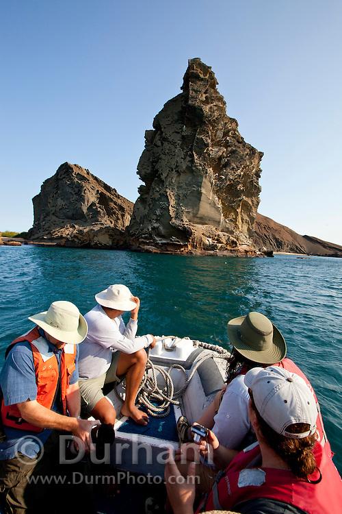 Tourists head toward Pinnacle Rock on Bartolome island, Galapagos Archipelago - Ecuador.