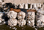 Paper collectors: A man sleeps atop a bunch of sacks full of recycled paper recovered from Rio de janeiro's business district. At times there are entire families living off the collection and recycling of paper at this centre, Brazil. JULY 1994