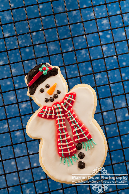 Closeup of Christmas snowman sugar cookie decorated with a black hat, carrot nose, and green tie.