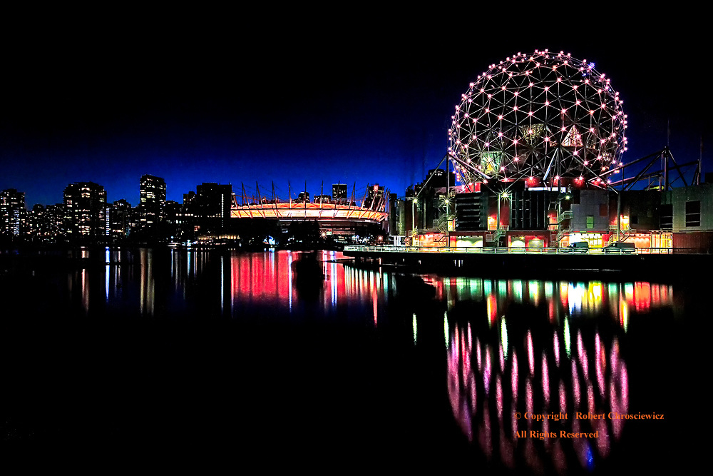 Night-False Creek: The distinctively circular Science World is reflected at dusk in False Creek, as downtown is cast in silhouette, Vancouver British Columbia Canada.