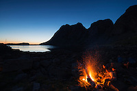 Evening campfire on the shore of Buvågen bay at Helle on the westernmost tip of Moskenesøy, Lofoten Islands, Norway