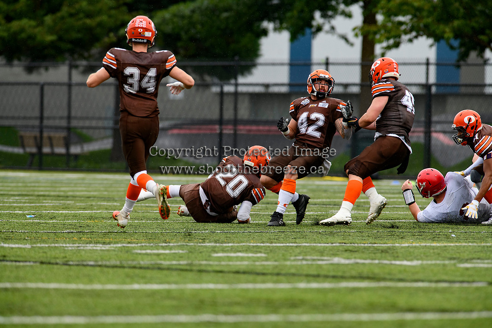 CHILLIWACK, BC - SEPTEMBER 11: Donavon Downing #47 tackles as Tyler Going #20 of Okanagan Sun runs in to intercept the ball from the Westshore Rebels at Exhibition Stadium in Chilliwack, BC, Canada. (Photo by Marissa Baecker/Shoot the Breeze)