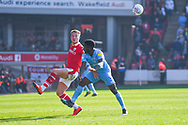Cauley Woodrow of Barnsley (9) and Brandon Mason of Coventry City (3) in action during the EFL Sky Bet League 1 match between Barnsley and Coventry City at Oakwell, Barnsley, England on 30 March 2019.