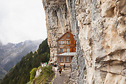 The Berggasthaus Aescher-Wildkirchli is a 170-year-old Swiss guesthouse built into the side of a mountain in Wasserauen, Switzerland. Photographed in 2017.