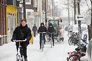 In Utrecht rijden fietsers voor een sneeuwschuiver op het fietspad. Nederland geniet van de eerste sneeuw sinds lange tijd.<br /> <br /> In Utrecht cyclists ride in front of a snowplow on a bike lane. People in the Netherlands enjoy the first snow since years.