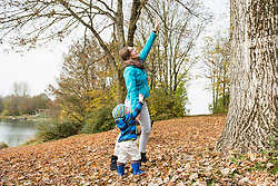 Mother and son trying to reach branches of big tree in autumn scenery