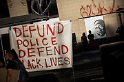 """OAKLAND, CA - JUNE 03: Demonstrators hang a sign next to a mural (back R) of George Floyd, who died in Minneapolis on May 25 whilst in police custody, during a """"Sit Out the Curfew"""" protest in downtown Oakland, California on June 3, 2020. - US protesters welcomed new charges against Minneapolis officers in the killing of African-American man George Floyd -- but thousands still marched in cities across the country for a ninth straight night, chanting against racism and police brutality. (Photo by Philip Pacheco/Agence-France Presse/AFP)"""