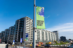 Glasgow, Scotland, UK. 21st October 2021. Final preparations underway at the site of the UN Climate Change Conference COP26 to be held in Glasgow from Oct 31st. Pic; A COP26 banner and residential apartment block to rear. Accommodation shortage in Glasgow is a major problem in the run up to the conference.  Iain Masterton/Alamy Live News.