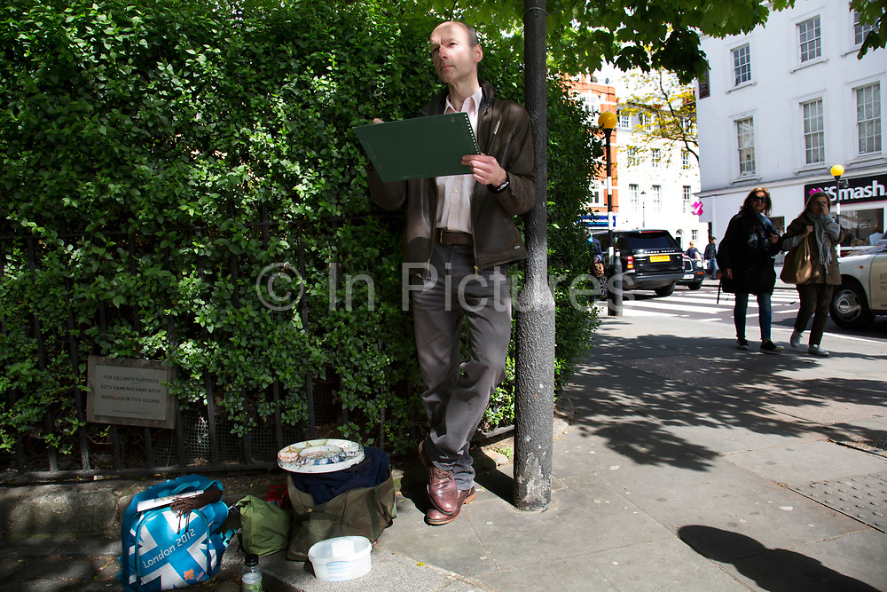 Andrew Horrod, a fine artist based in West London, painting on a street corner on the Kings Road in Chelsea. London, England, UK.