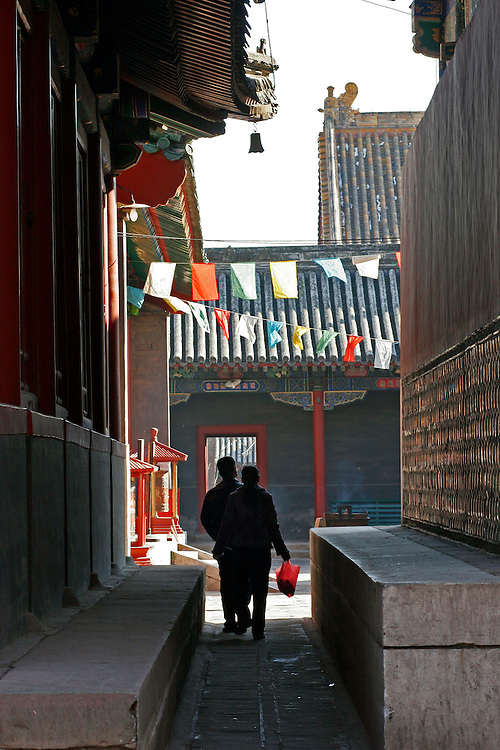 Beijing China 2007 Worshipers exit the fifth courtyard through a small alleyway underneath strings of prayer flags at Yong He Gong March 7, 2007.  This Tibetan Temple is known to tourists as Lama Temple and it's located in Dongcheng District Beijing, China. This is the largest Temple of its kind outside of Tibet.  In 1723 the structure was turned into a Temple after the resident became the third Qing Emperor.