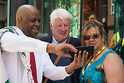 Windrush campaigners Anthony Brown and Julia Davidson pose for a selfie with a passing Stanley Johnson, father of Prime Minister Boris Johnson, at the beginning of a Windrush protest march from the Home Office to the Houses of Parliament on 23rd June 2021 in London, United Kingdom. The campaigners are calling for a new independent body, and not the Home Office, to administer the scheme intended by the government to compensate them for the violation of their rights. Many legal residents who came to the UK from the Caribbean lost their homes, jobs and other rights after having been targeted by the Home Office.