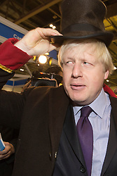 """© Licensed to London News Pictures. 22/11/2013. London, England. Pictured: Boris Johnson dons the uniform of a doorman. Boris Johnson, Mayor of London, today visited the UK's biggest jobs and careers fair """"Skills London"""" at the Excel Exhibition Centre and went on a walkabout where he visited stands and performed some of the jobs on show. Photo credit: Bettina Strenske/LNP"""