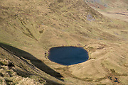 Llyn Cwm Llwch lake from the summit of Pen Y Fan mountain in Brecon Beacons National Park, Wales, Powys, United Kingdom.  Llyn Cwm Llwch is the best preserved glacial lake in South Wales and sits right at the head of the Cwm Llwch valley – part of the Brecon Beacons Site of Special Scientific Interest SSSI and a Geological Conservation Review GCR site granted because of the special contribution they make to Britain's geological history.