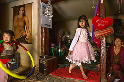 In the family living room, Unika plays with her younger brother as her parents debate whether to offer her for selection as a kumari. The incumbent girl had just been dismissed because she got her first period.