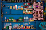 A detail of drinks and snacks on sale on blue shelving opposite the ancient Egyptian heritage site of the Colossi of Memnon on the West Bank of Luxor, Nile Valley, Egypt.