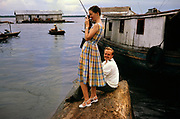 Tourists visiting area of informal housing wooden shacks built on timber logs known as the Floating City, Manaus, Brazil 1962 - woman taking photograph